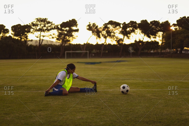 Side view of African-American female soccer player doing warm-up exercises at sports field during tournament