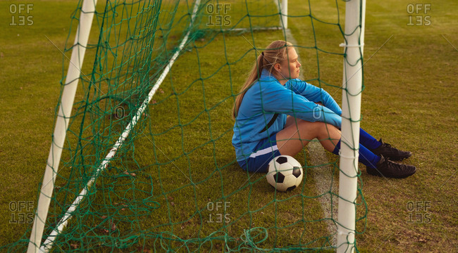 Side view of thoughtful Caucasian female soccer player relaxing at sports field