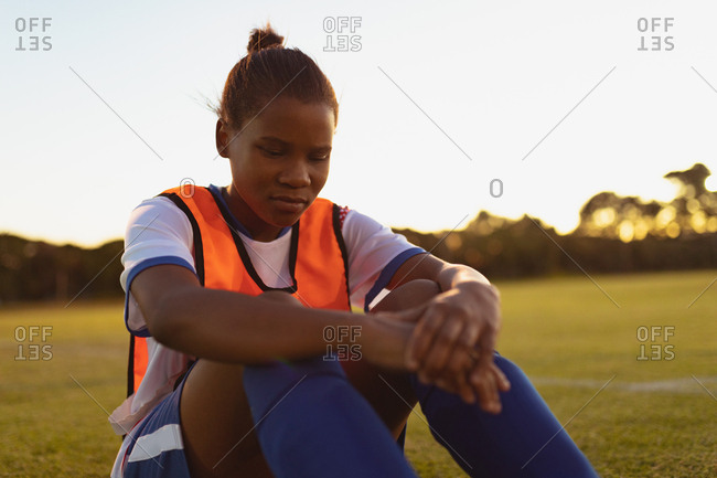 Front view of African-American female soccer player relaxing on grass at sports field