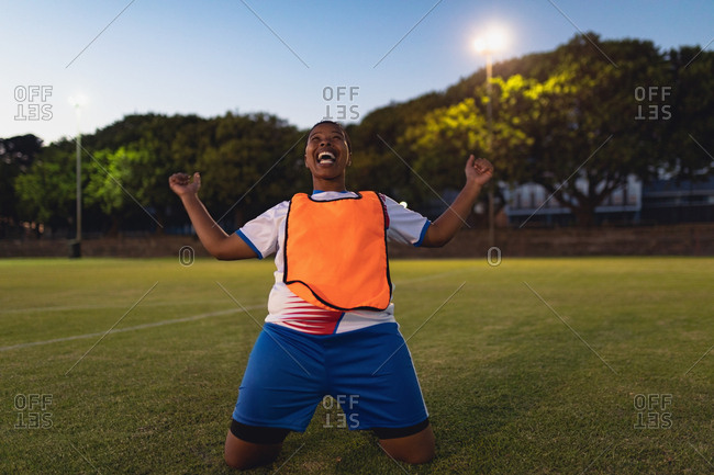 Front view of carefree African-American female soccer player cheering after victory at sports field