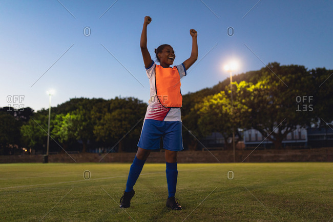 Low angle view of carefree African-American female soccer player cheering after victory at sports field