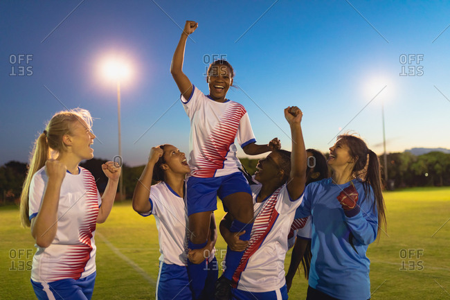 Front view of diverse female soccer team cheering on their victory at sports field