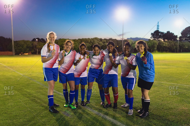Front view of diverse female soccer team posing with medal at sports field