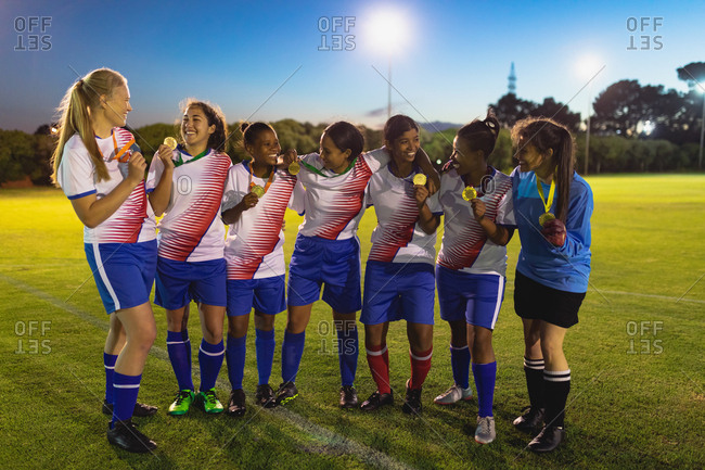 Front view of diverse female soccer team showing medal to each other at sports field