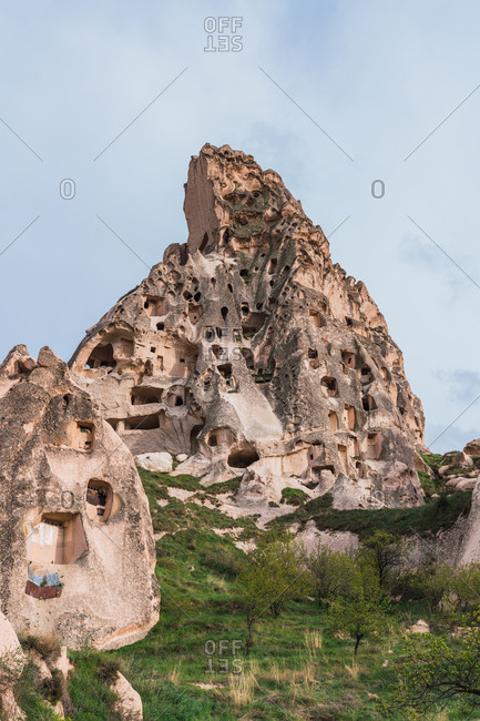 Scenic view of ancient dwellings carved into rock of Cappadocia in Turkey on background of blue sky