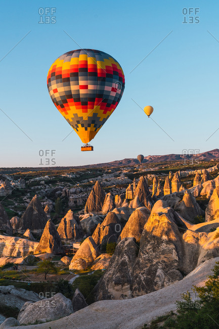 May 30, 2019: Bright hot air balloons flying against cloudless evening sky over stone formations in Cappadocia, Turkey