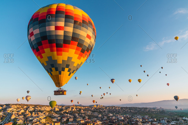 May 30, 2019: Many colorful hot air balloons flying over buildings of city against cloudless evening sky in Cappadocia, Turkey