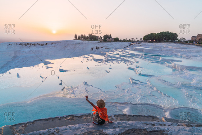 From above back view of male raising hand, sitting on carbonate terrace near hot springs in sunset at Pamukkale, Turkey