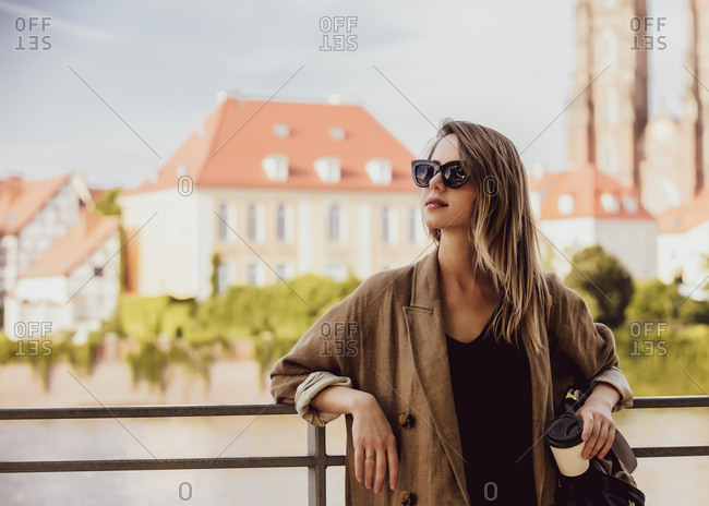 Young style woman in sunglasses stay near railing with old city on background