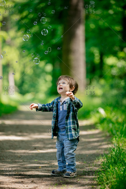little toddler boy stands on a footpath in the forest