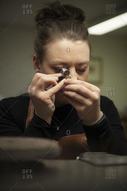 Female goldsmith examining gold through loupe at workshop