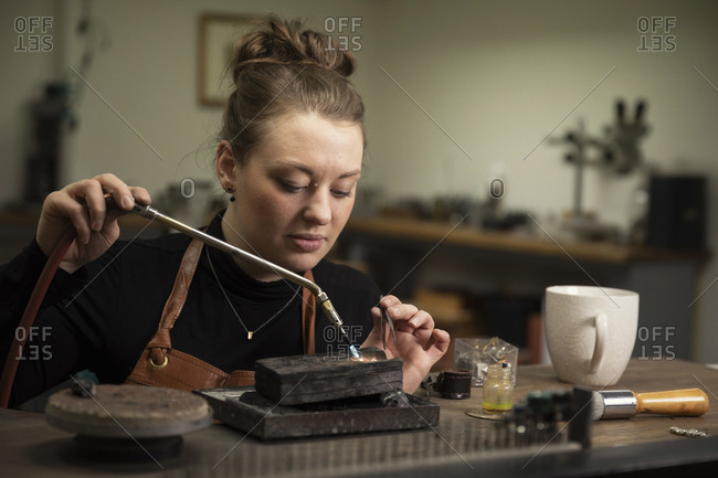 Female goldsmith heating metal with welding torch to make jewelry at workshop
