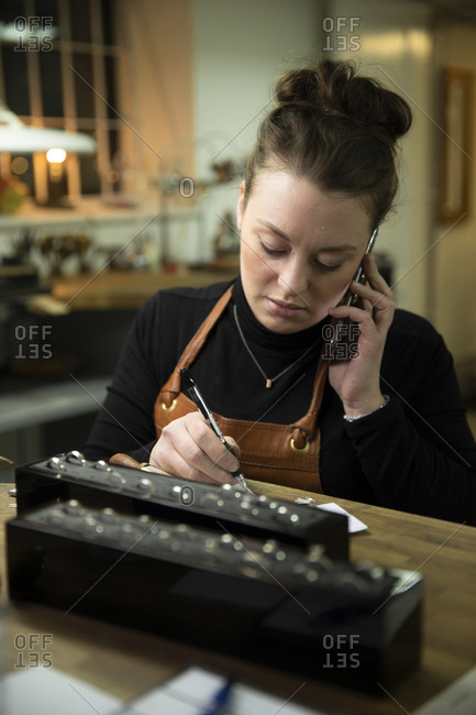 Female goldsmith taking order through mobile phone while sitting at workbench in workshop