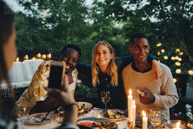 Woman photographing happy male and female friends sitting at table during dinner party
