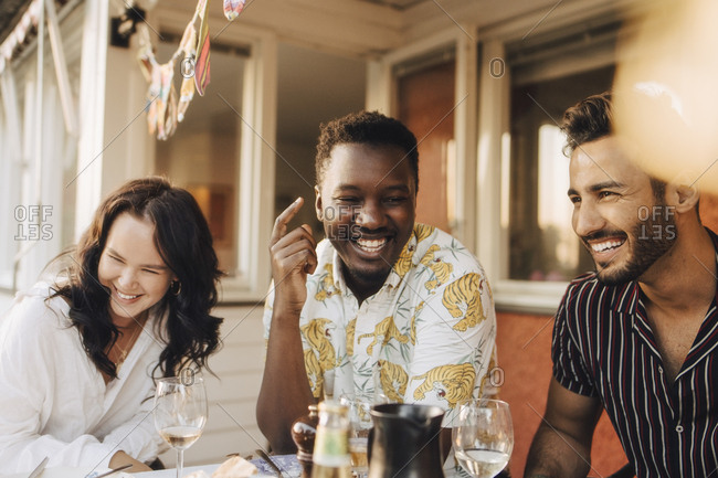 Cheerful friends having fun at dining table during dinner party