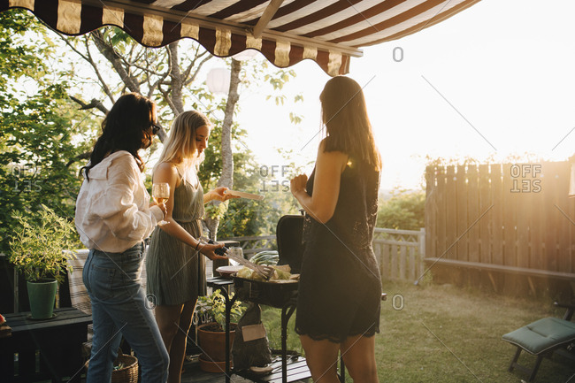 Female friends talking while preparing food on barbecue grill in dinner party