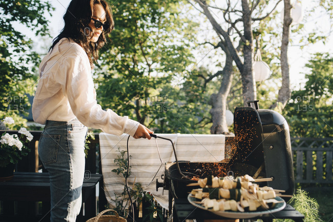 Woman grilling food on barbecue at yard during summer