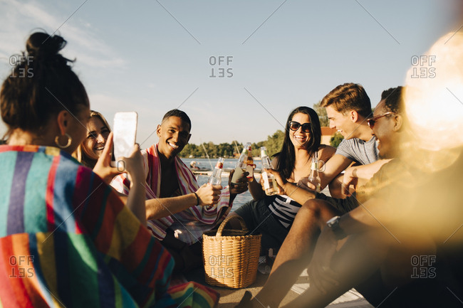 Woman photographing cheerful friends toasting drinks at jetty in summer