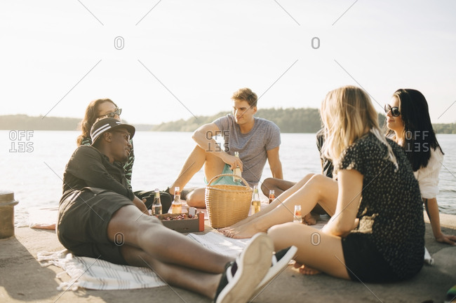 Multi-ethnic friends enjoying food and drink while sitting on jetty at lake against sky