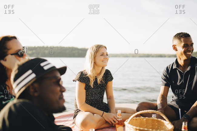 Cheerful multi-ethnic friends talking while sitting on jetty at lake in summer