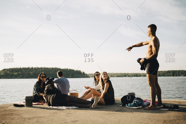 Shirtless man pointing while talking to friends on jetty at lake against sky