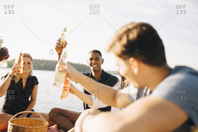 Friends enjoying drinks while sitting on jetty against sky in summer