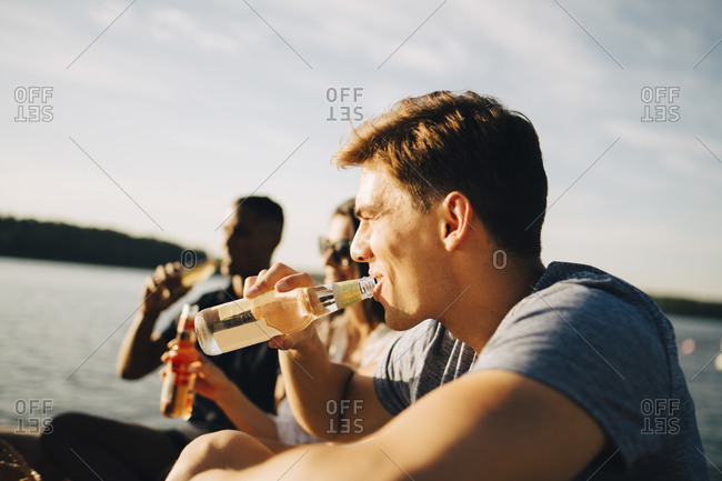 Man enjoying drink with friends while sitting on jetty against sky in summer