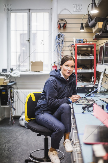 Portrait of mature female technician sitting in electronics store