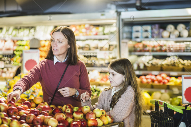 Mother and daughter choosing fresh apples at market stall