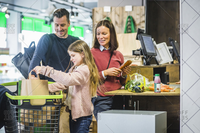 Smiling parents looking at daughter arranging paper bags in shopping cart