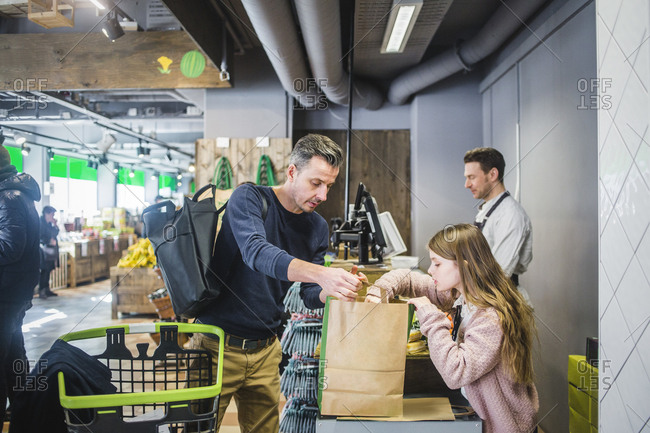 Father and daughter packing groceries in paper bag at checkout counter