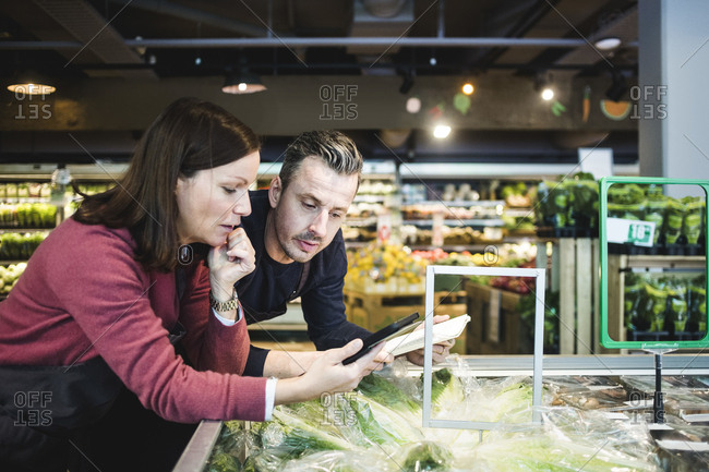 Sales clerks using digital tablet at market stall in supermarket
