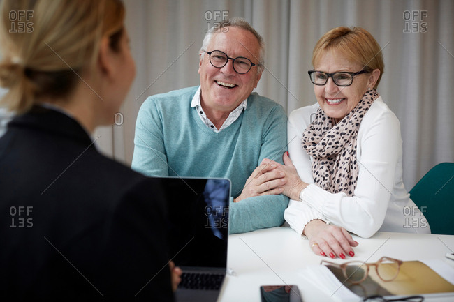 Happy senior couple talking to real estate agent in office