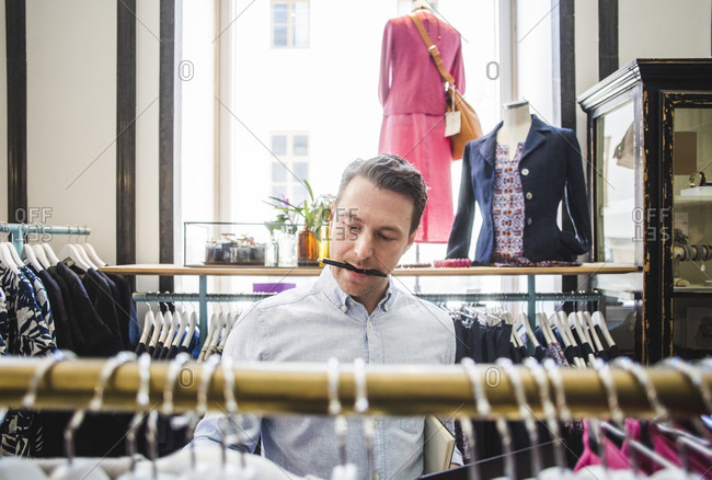 Salesman carrying pen in mouth while looking at clothes rack