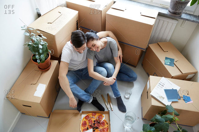 High angle view of couple resting together while having pizza during relocation of new house