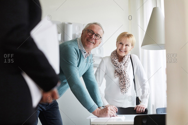 Smiling senior couple looking at real estate agent while signing for new house