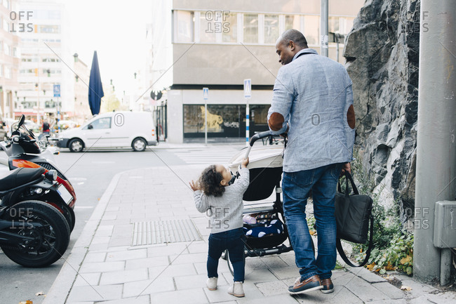Full length of father talking to daughter while walking with carriage on sidewalk in city
