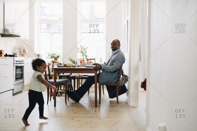 Father working on laptop while daughter playing in kitchen