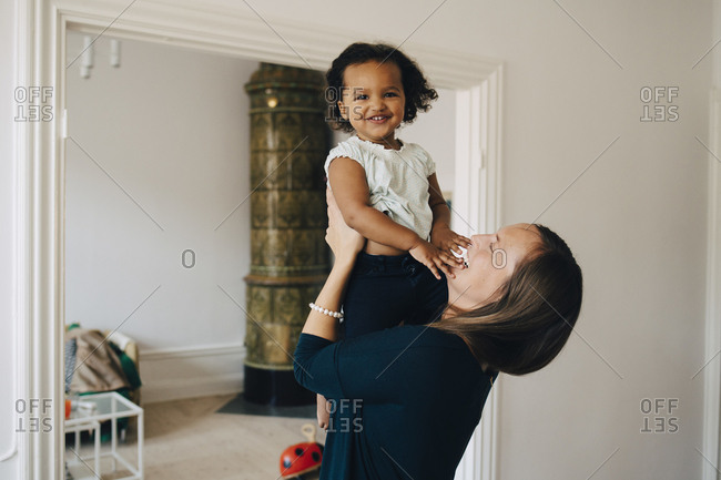 Happy mother holding daughter while standing at home