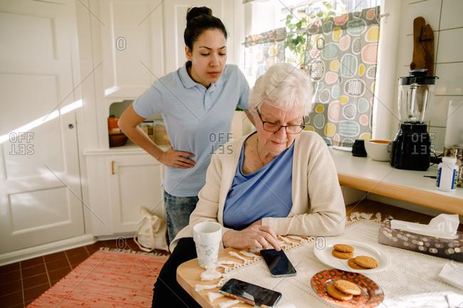 Young female volunteer looking at retired elderly woman using smart phone in nursing home