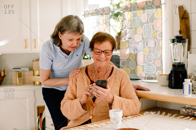 Mature female volunteer standing by smiling senior woman using mobile phone in kitchen at nursing home