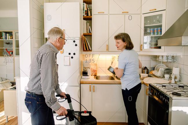 Retired senior man talking to female volunteer washing dishes in kitchen at nursing home