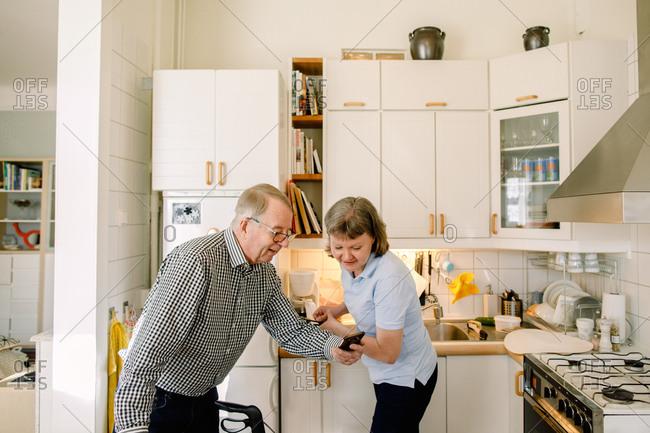 Retired senior man showing smart phone to female volunteer washing dishes in kitchen at nursing home