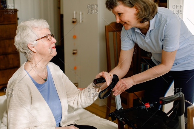 Smiling female healthcare worker looking at senior woman sitting with rollator in bedroom at nursing home