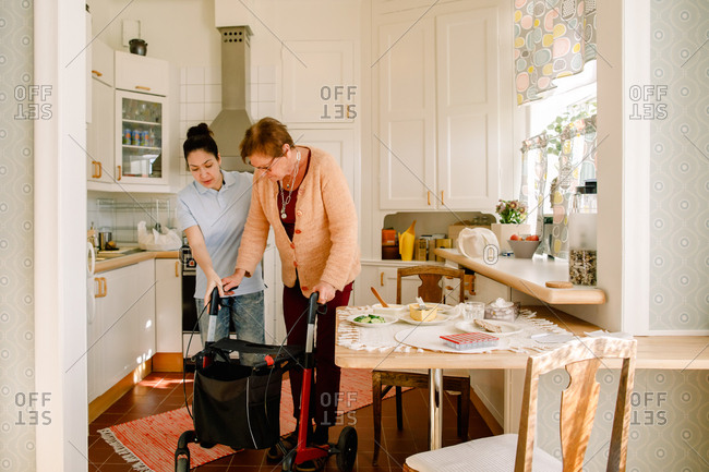 Young female volunteer assisting retired elderly woman with rollator in kitchen at nursing home