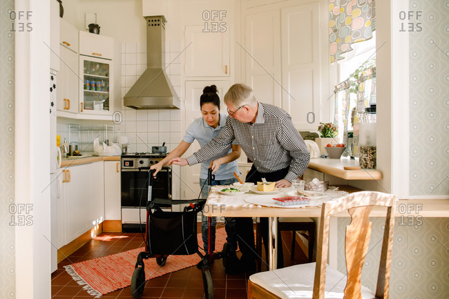 Young female volunteer assisting retired elderly man with rollator in kitchen at nursing home