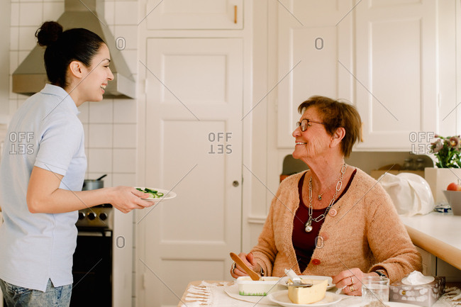 Happy elderly woman talking with female healthcare worker in kitchen at nursing home