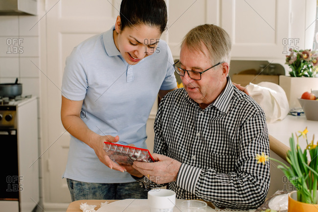 Smiling young female social worker explaining medicines to retired senior man in nursing home
