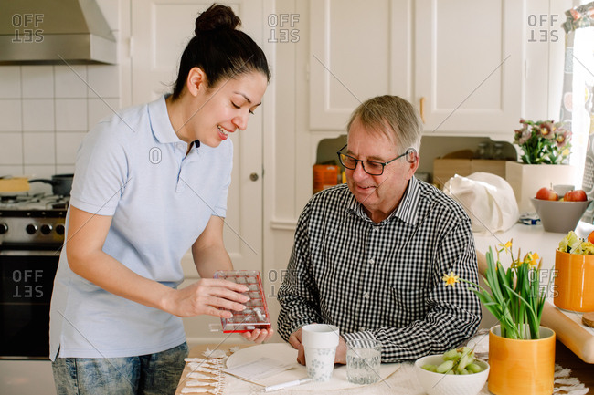 Smiling young female healthcare worker explaining medicines to retired elderly man sitting at table in nursing home