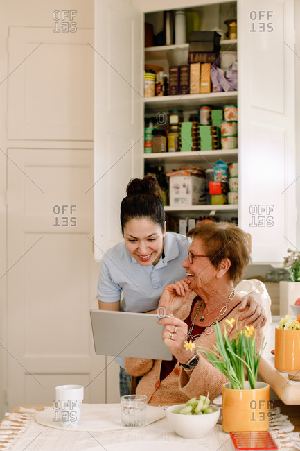 Smiling elderly woman sharing digital tablet with young female caregiver working in kitchen at nursing home
